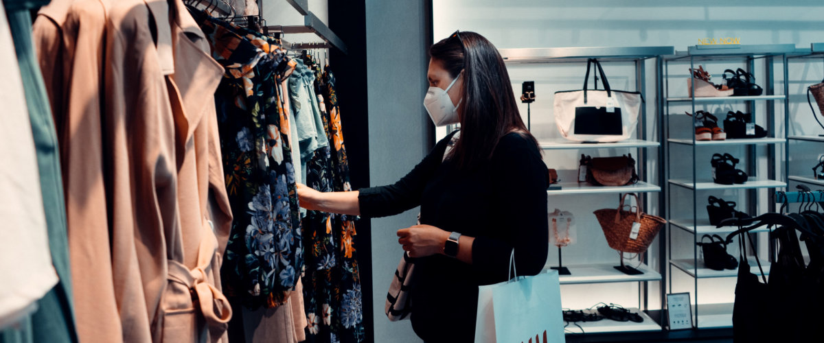 A woman shopping at a boutique hile wearing a face mask. Photo by Arturo Rey on Unsplash