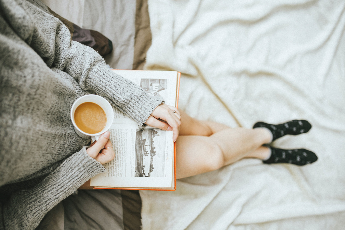 Woman reading a book and enjoying a cup of coffee. Photo by Anthony Tran on Unsplash.
