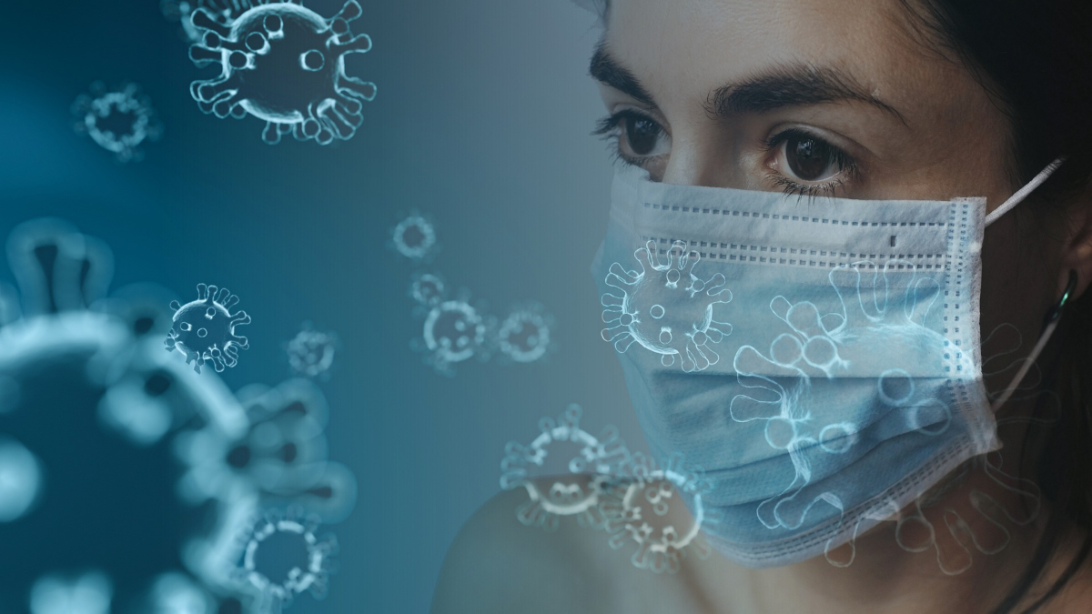 Illustration of coronavirus and a woman in a mask. Image by Tumisu from Pixabay