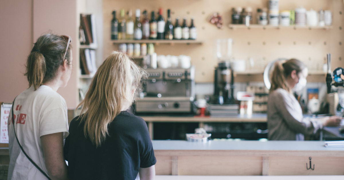 Two women wait for their order, being prepared by a sever wearing a face mask. Photo by Dan Burton on Unsplash.