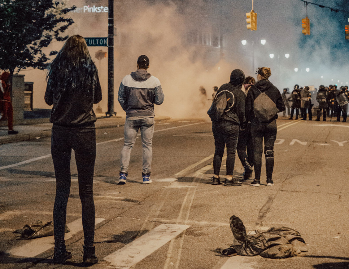 protesters face cops and teargas