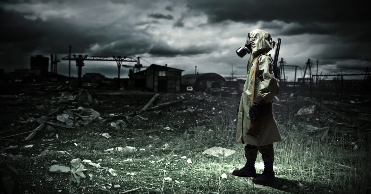 Man with gas mask and gun in a wasteland