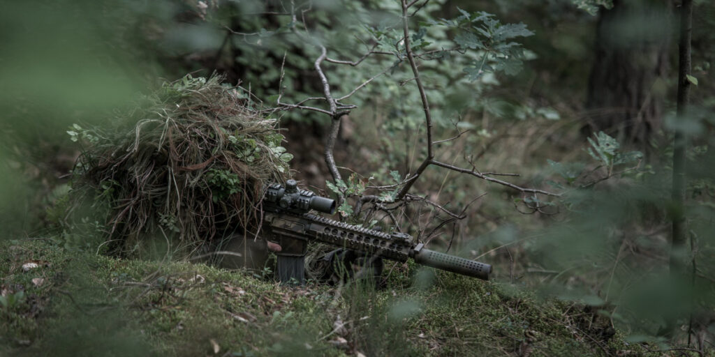 camouflaged shooter in ghilliesuit
