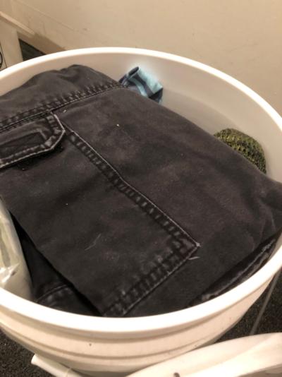 Folded pants in a bucket.
