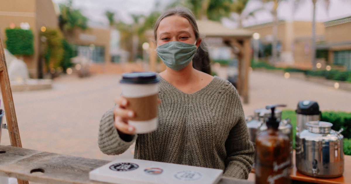 Mask wearer serving coffee. Photo by Vince Fleming on Unsplash.