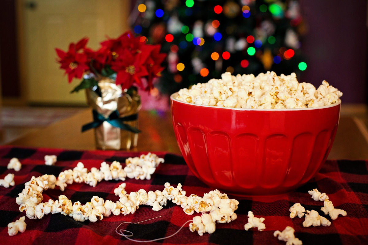 Popcorn in a bowl with a Christmas tree in the background. Photo by Jill Wellington from Pixabay.