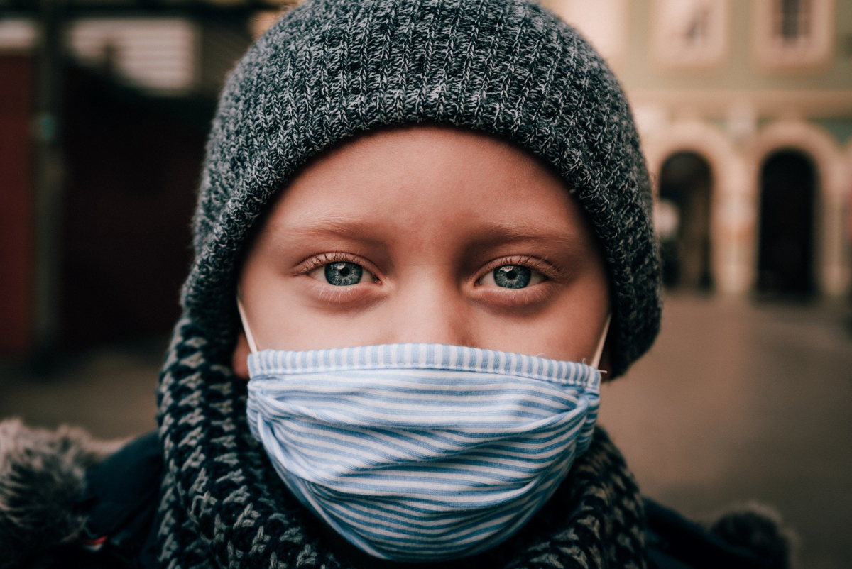 blue-eyed child in face mask and warm hat. Image by René Bittner from Pixabay.