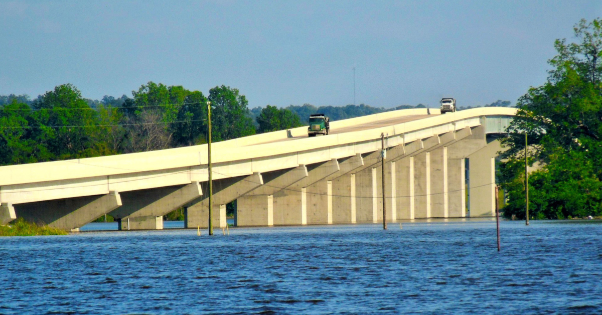 Dump trucks cross a bridge over the Mississippi River. Image by Mistyck Moon from Pixabay.