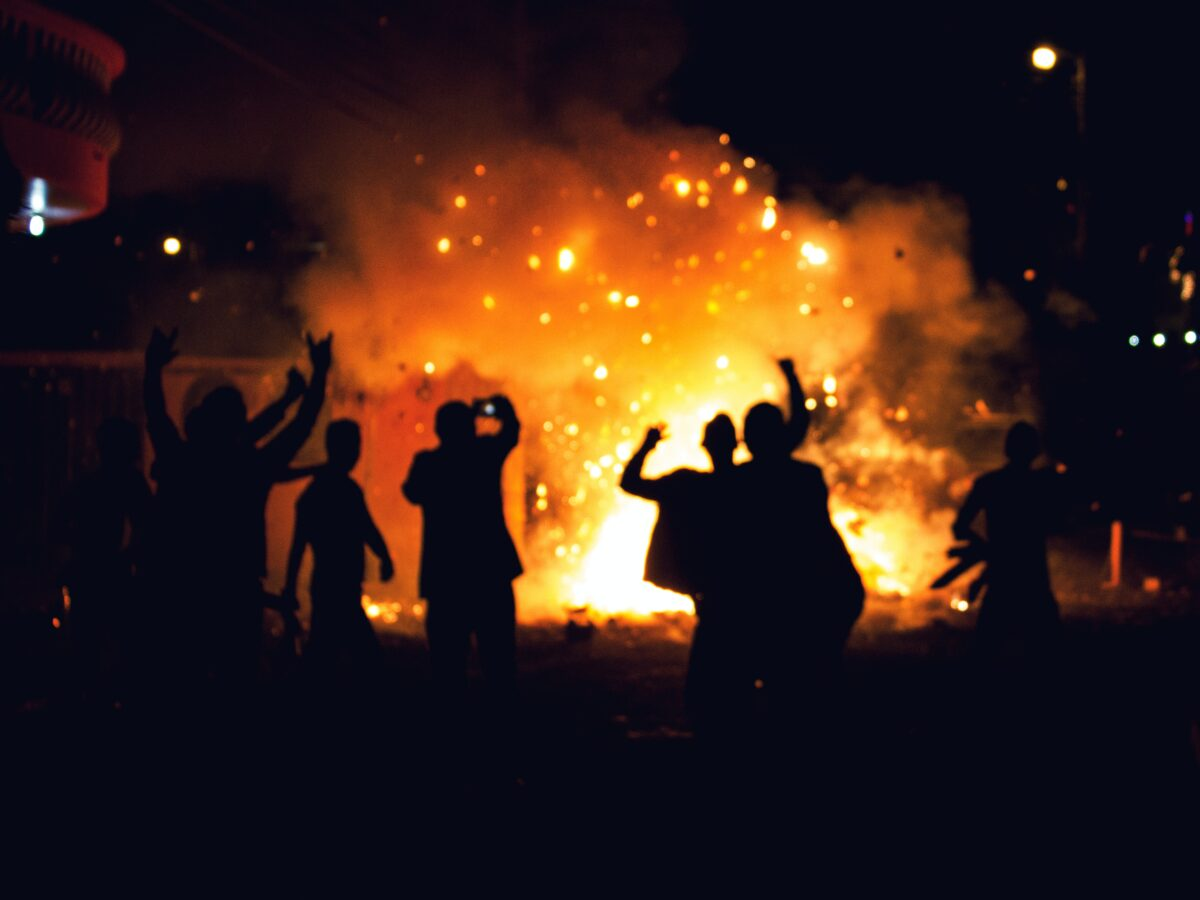 Rioters enjoy the flames of arson. Photo by Alex McCarthy on Unsplash.