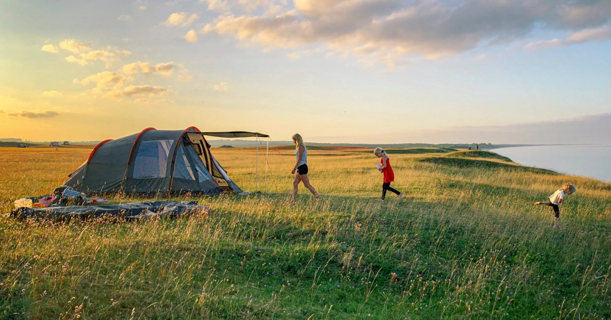 A family camping in a tent. Photo by Mattias Helge on Unsplash.