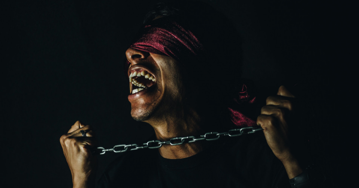 A blindfolded man in chains. Photo by Tony Rojas on Unsplash.