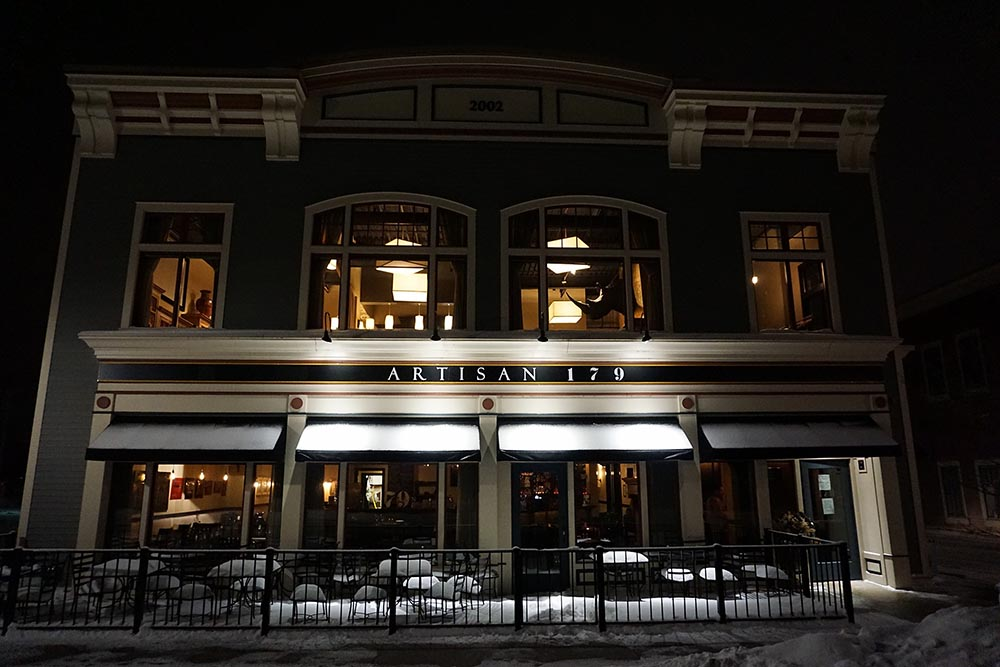 Front facade of Artisan 179 restaurant at night with snow covering the ground with lights from interior glowing