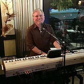 Man playing keyboard in front of window with microphone
