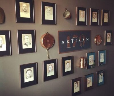 Wall art with Artisan 179 logo centered surrounded by various drawings of people and cookware on wall