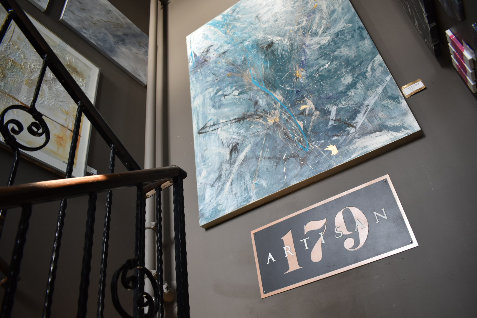 Stairwell with Artisan wall logo and various art pieces on the wall