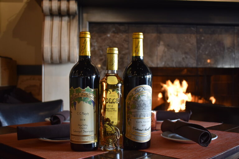 Wine bottles positioned on table in front of fireplace