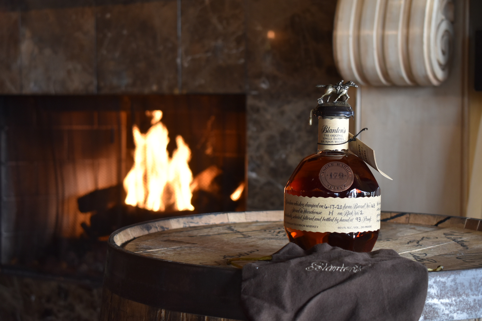 Bottle of Blanton's with Artisan 179 label on it sitting on barrel in front of fireplace