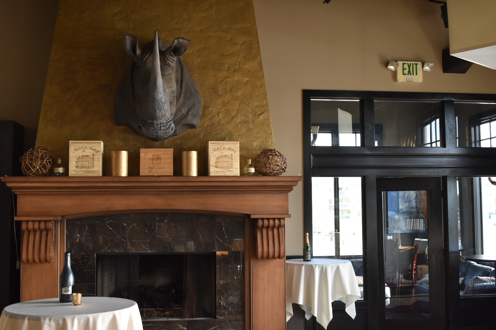 Rhino Room featuring fireplace with Rhino overhead and tables with wine bottles on top and exit door