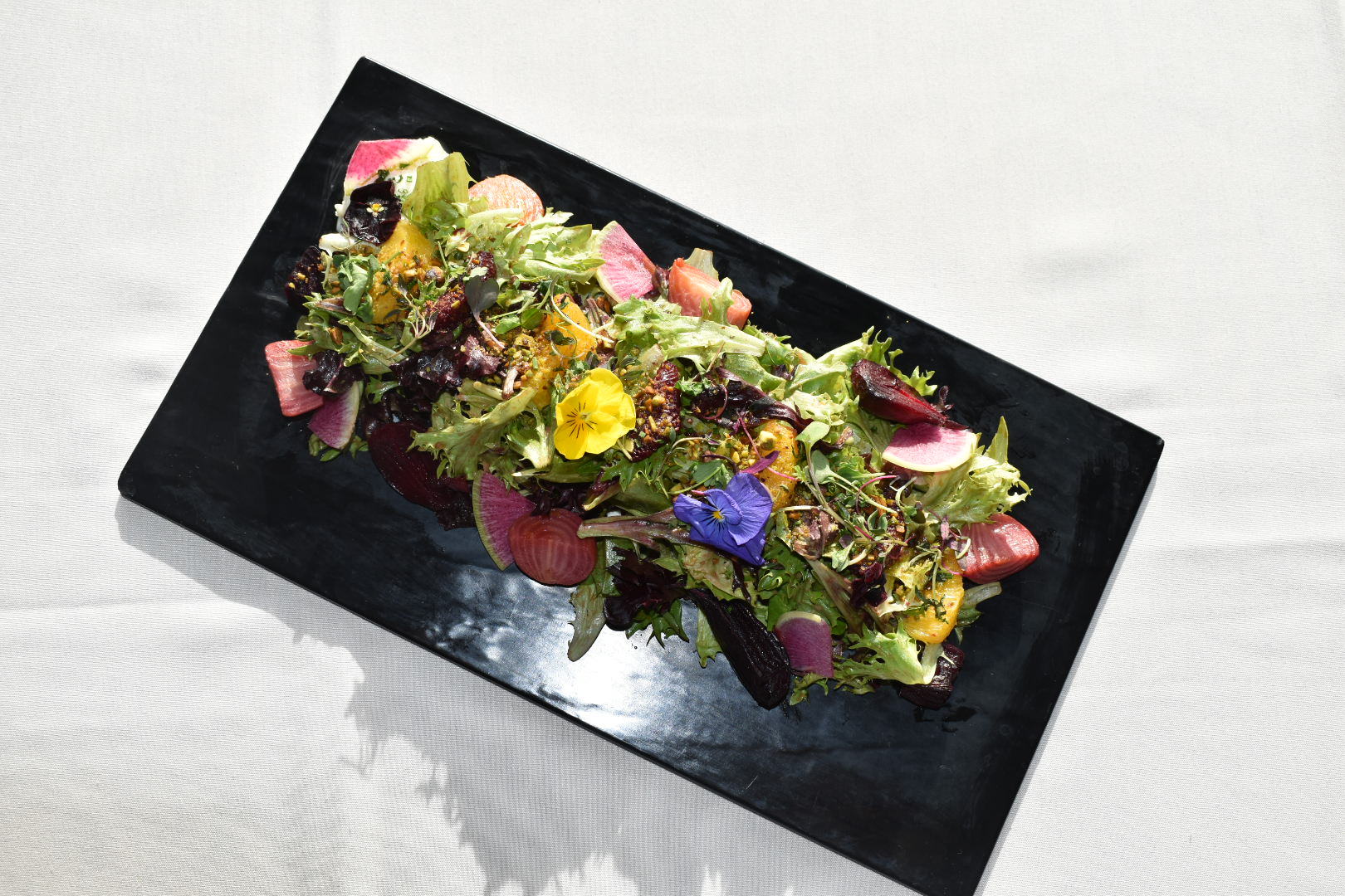 Colorful citrus beet salad with edible flowers on top of table