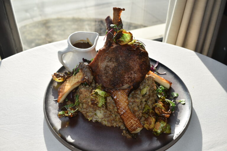 Dish of Heritage Berkshire Double Bone-in Pork Chop on table in front of window with pan-seared King Trumpet mushrooms, risotto de farro, black garlic pork demi, shaved brussels