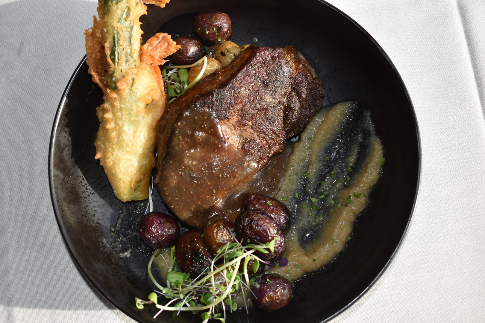 Plate of food featuring a New York Strip steak, battered leek, potatoes, and greens