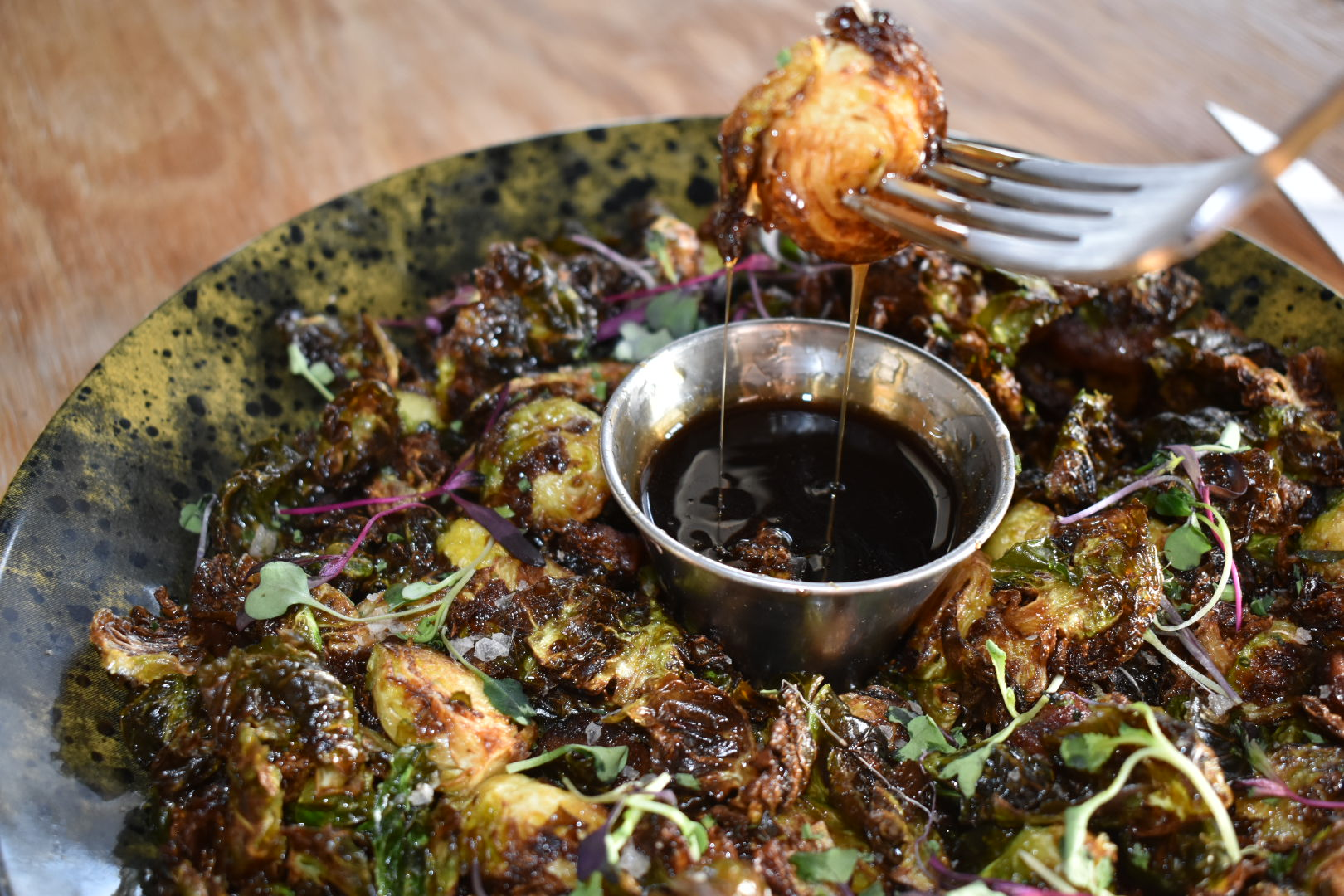 Fork elevating Brussel sprout in carmelized glaze dripping into sauce dish