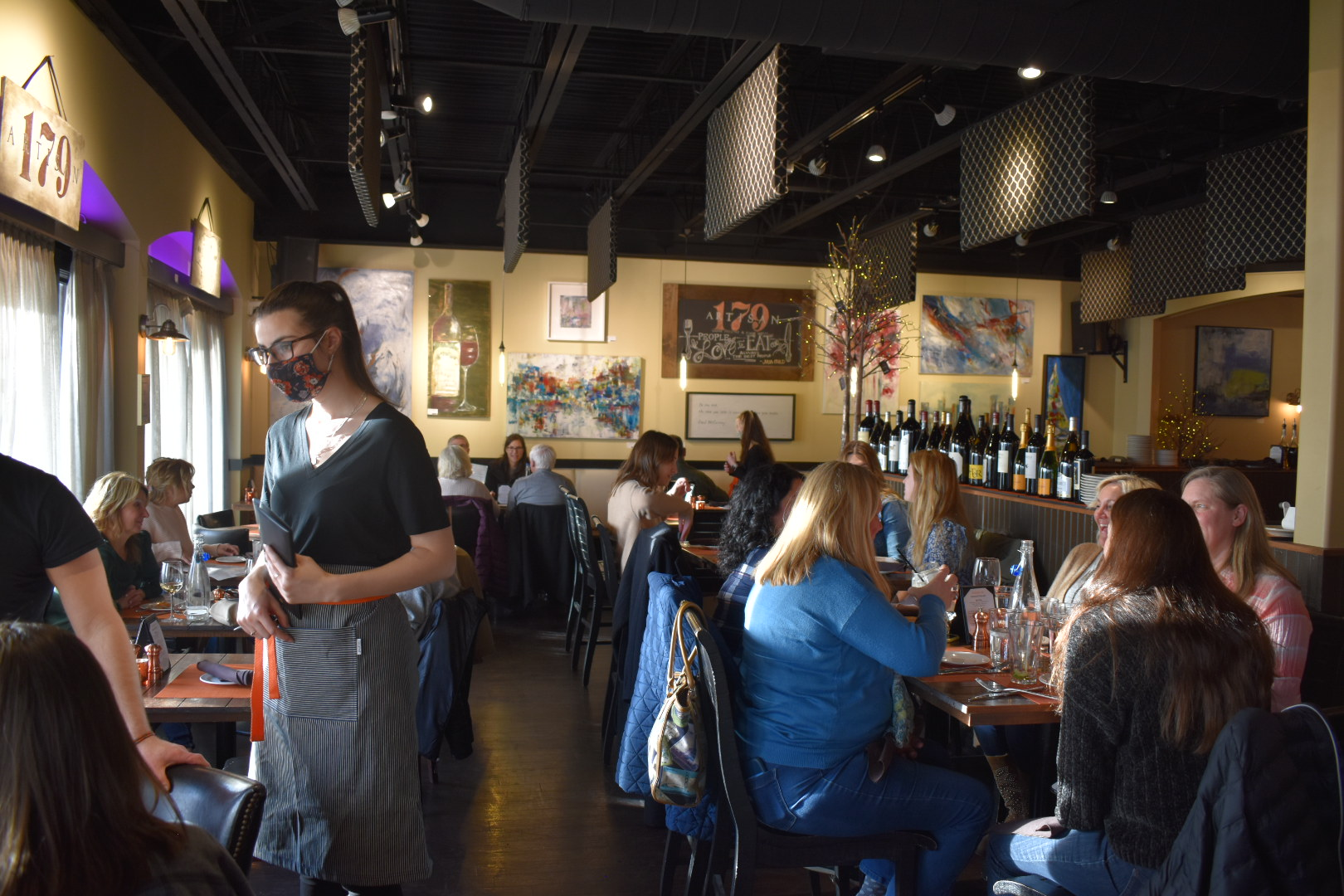 Waitress wearing mask serving table in busy Artisan 179 restaurant for early dinner while people at various tables are talking