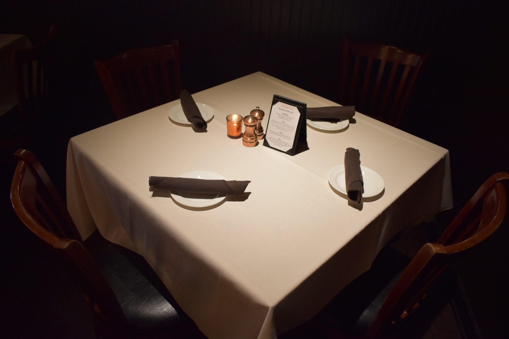 linen-covered table with plates and silverware with menu shakers and candle on table with dark ambience