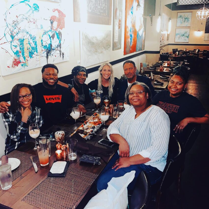 Group of people enjoying food and beverages with wall art in background