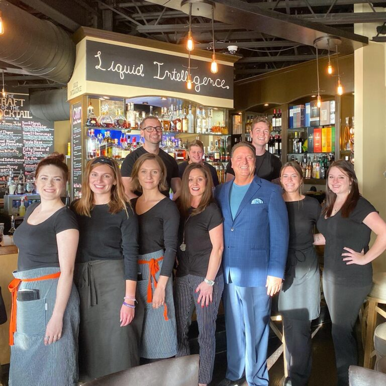 Group of team members, bartenders, waitresses, standing and smiling in front of bar