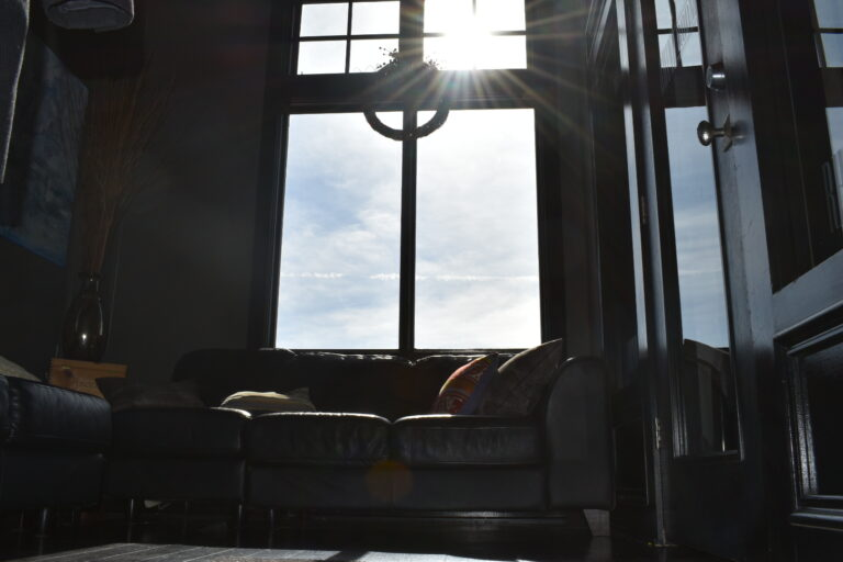 angled shot of couch in front of window with sun shining into room, creating glare
