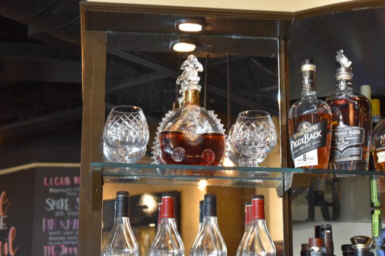 Liquor flask of Louis XIII Cognac and glasses alongside other bottles of liquor