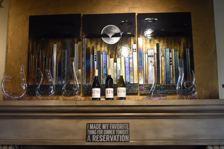 Wine bottles with Artisan 179 label atop fireplace mantel with liquor decanters and artwork of Manhattan skyline