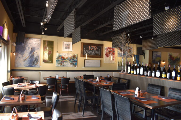 several tables and chairs set for dining with artwork on the wall