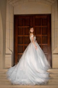 bride wearing a beautiful off the shoulder ball gown wedding dress, white lace cathedral train princess dress