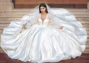 Bride seated with a big wide puffy Ivory wedding dress with a nice long cathedral veil holding a bridal bouquet, this beautiful long lace sleeves sating ball gown