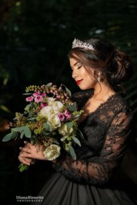 Beautiful bide wearing a long sleeve black gown smelling her roses