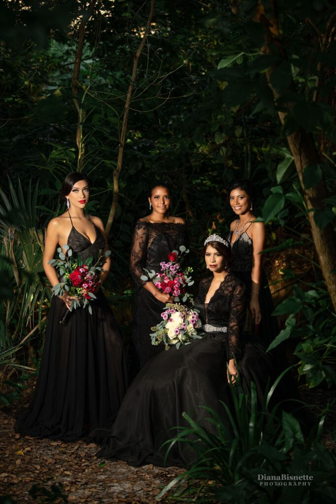 Whimsical bride in a garden in a black wedding dress, holding a beautiful bridal bouquet,