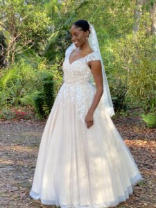 Bride wearing a Floor length Wedding dress, Ball gown nude color with I vory lace