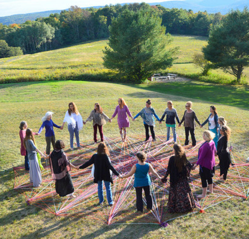 women in a field doing circlework