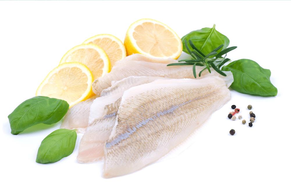 fresh fish filet, lemon slices and basil leaves