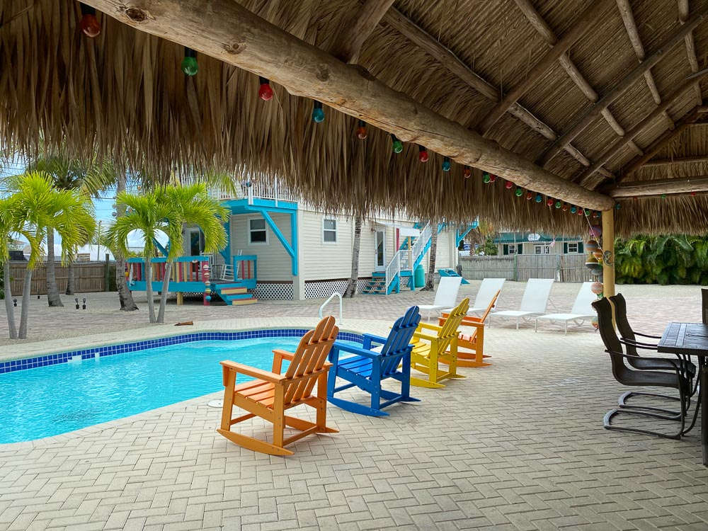 View of the sparkling pool with lounge chairs and rocking chairs poolside and steps away from the Tiki outside dining area in marathon florida vacation rental
