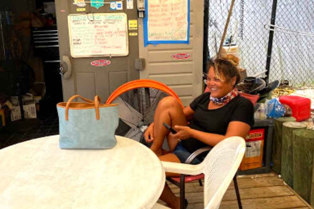 Smiling woman holding her cell phone, wearing a black shirt and shorts sitting on a patio chair with her purse on the tabletop and a dry erase sign hanging behind her with boat rental rates on the board in marathon florida