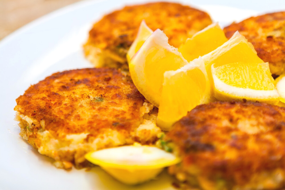 crab cakes on a white plate with lemon wedges on top in marathon florida