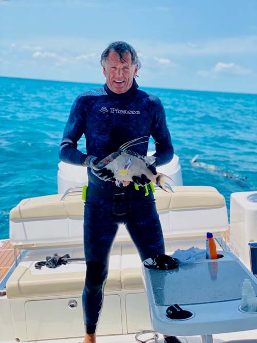 Man wearing scuba suit holding a hogfish caught in the Florida Keys