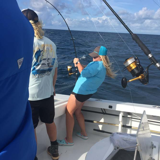Girl reeling in a fish from a boat in the Florida Keys