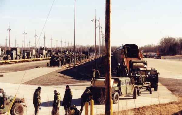 Army vehicles are loaded onto rail transport cars in the foreground. Meanwhile, in the background, army vehicles sit on flat cars ready to roll out.