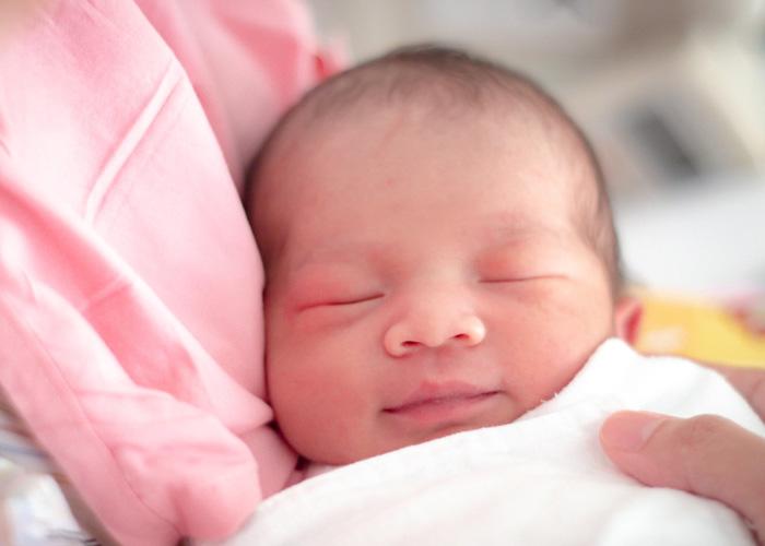 newborn baby being held close