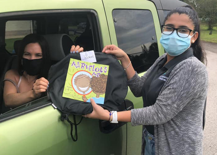 Champions for Children employee handing a mother a bag of supplies a book with a protective mask on