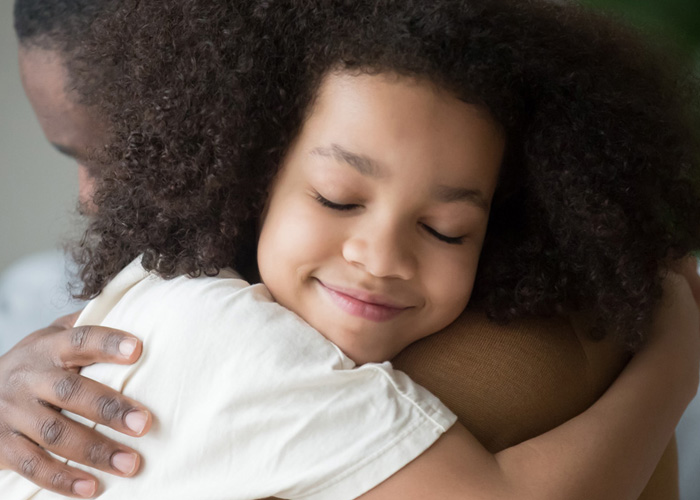 young girl smiling and hugging her dad with her eyes closed